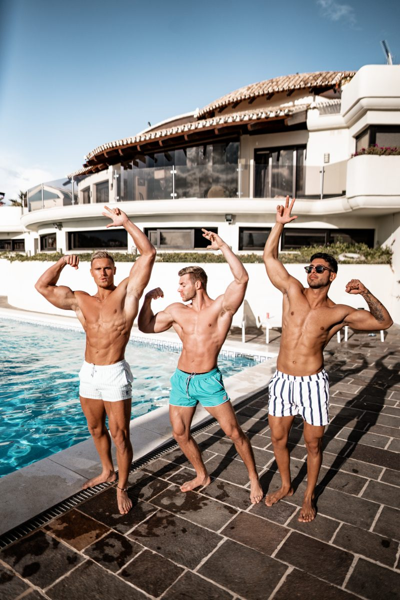 Guys flexing muscles in board shorts