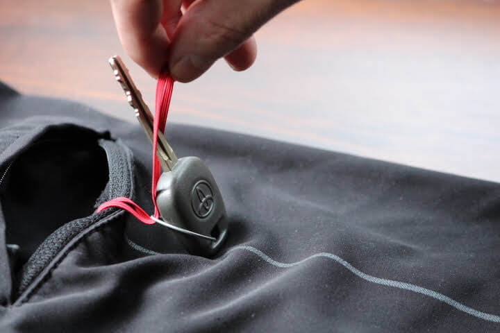 Step four in attaching a key to the key loop on your board shorts.