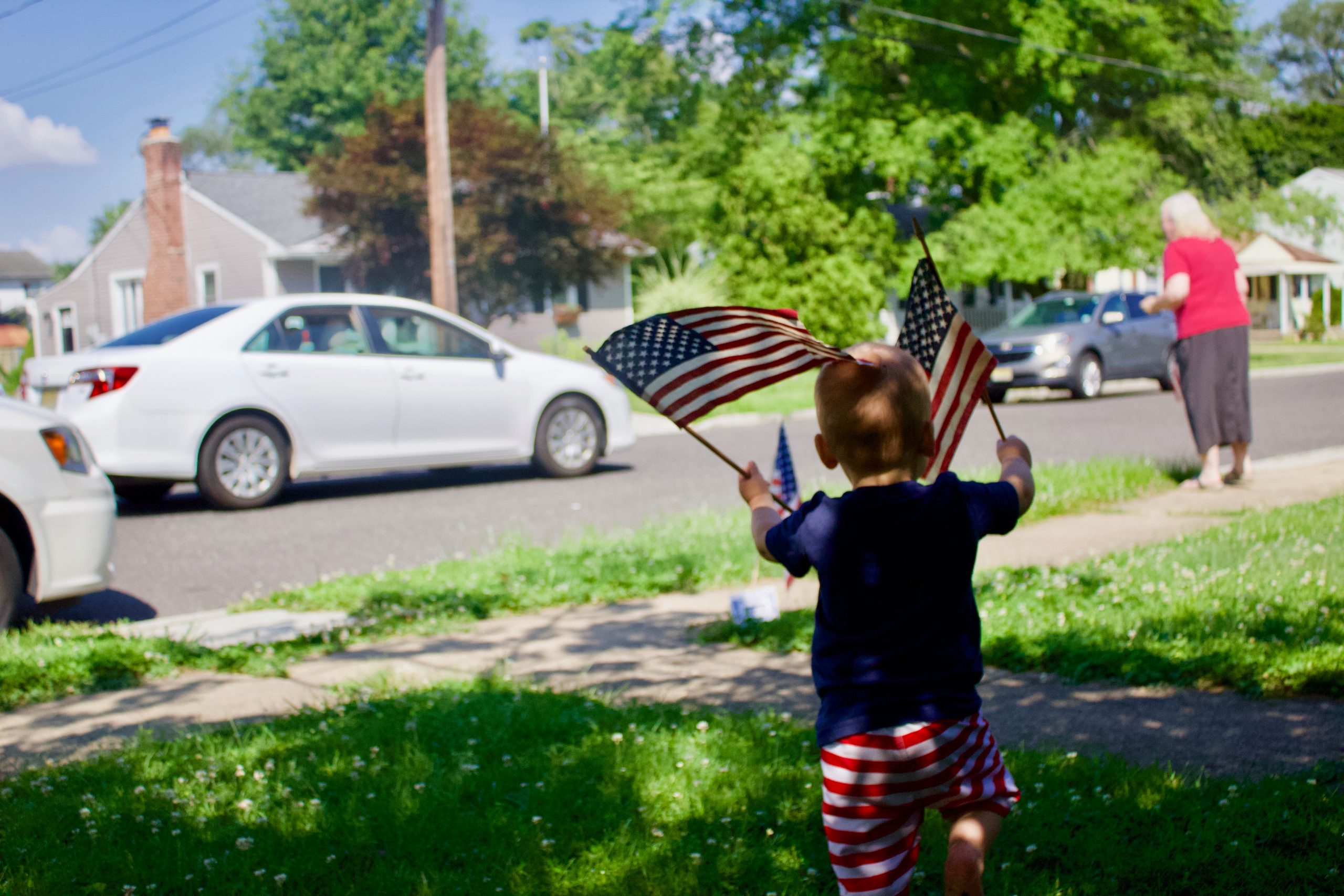 kid wearing american flag board shorts holding America flag during daytime