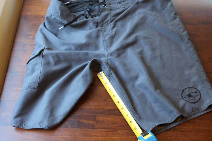 Measuring the inseam on a pair of shorts using a tap measure.