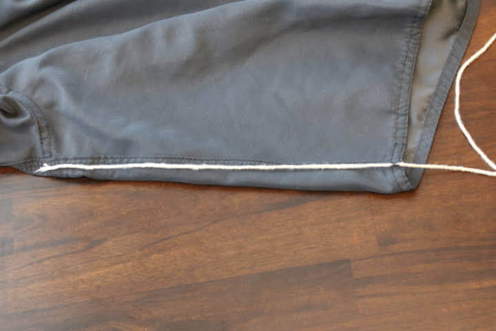 Measuring the inseam on a pair of shorts with string.