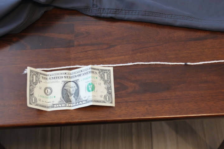 Using a dollar bill to measure the inseam on a pair of shorts