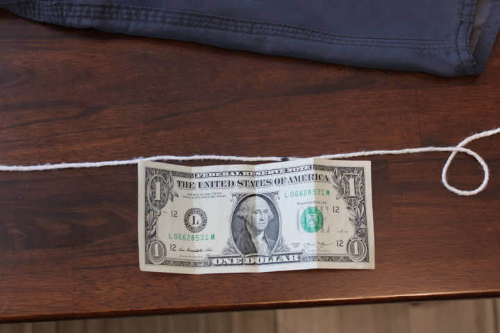 The mark on the string hits around the middle of the third fold on the dollar bill, close to 4 inches.