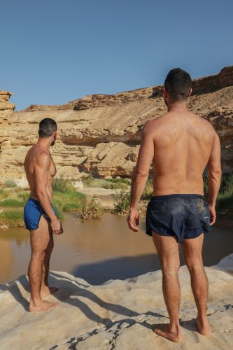 2 men standing on rock near body of water during daytime