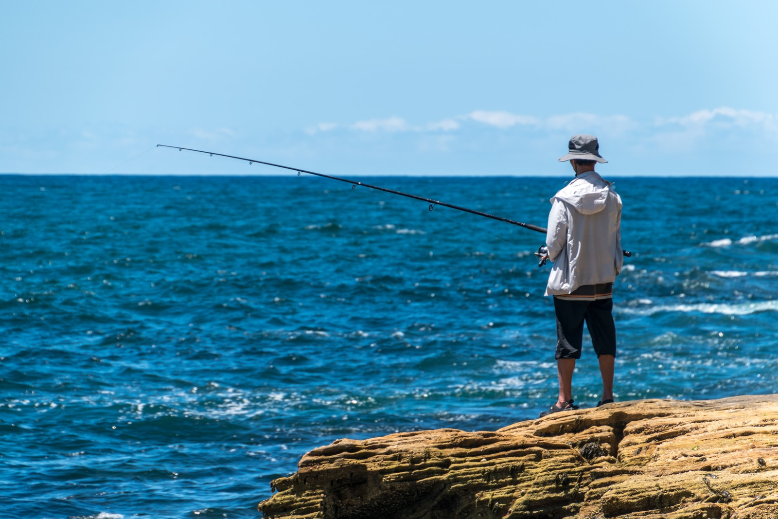man in white shirt and black shorts fishing on sea during daytime